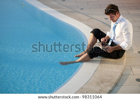 Young businessman working on PC tablet with feet in the pool