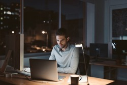 Young businessman working overtime alone at his desk in an office late at night with city lights glowing in the background