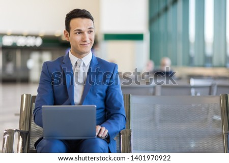 Young businessman working with his laptop in an airport #1401970922