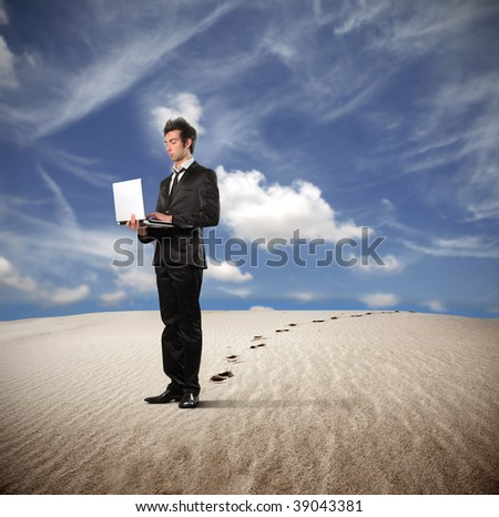 young businessman working with laptop in a desert - stock photo