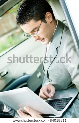 Young businessman working with laptop in the car
