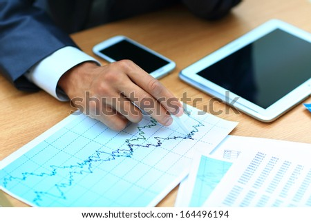 Young businessman working with modern devices, digital tablet computer and mobile phone.