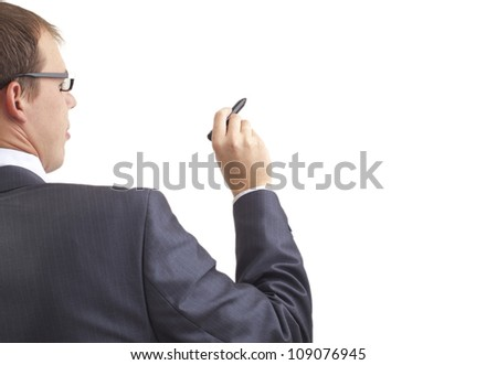 Young businessman writing something with a marker, back view