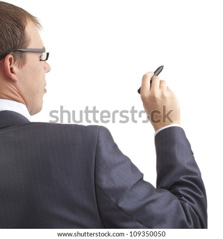Young businessman writing something with a marker, back view   Space for inscriptions