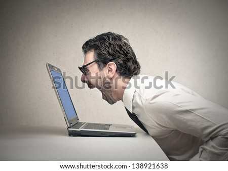 young businessman yells because he made a mistake on the computer - stock photo