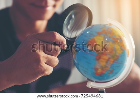 Young businessmen are looking through a magnifying glass to the globe to find a target audience. Look for or find a business target (concept) #725494681