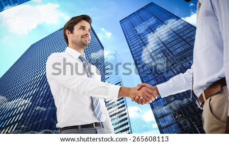 Young businessmen shaking hands in office against skyscraper #265608113