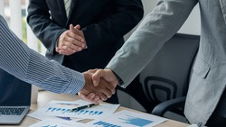 Young businessmen shaking hands in the office Completing a successful meeting Three-person model. In the office on a desk with a laptop and graph papers.
