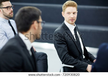 Young businessmen sharing their opinions about report points of speaker at conference