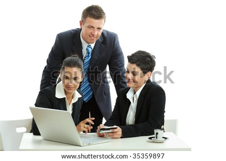 Young businesspeople at office desk, looking camera, smiling.