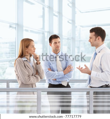 Young businesspeople chatting in modern office lobby.?