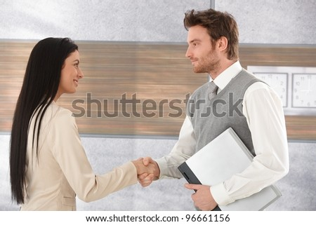 Young businesspeople greeting each other by shaking hands, smiling.?