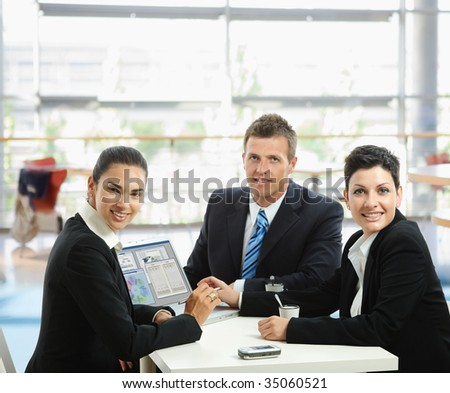 Young businesspeople having a business meeting at coffee table in office lobby, using laptop computer.