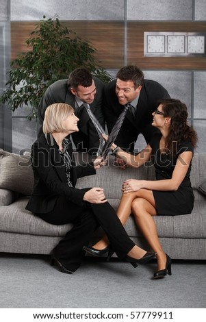 Young businesspeople having fun in office, sitting on couch. Women pulling businessmen's tie, laughing.?
