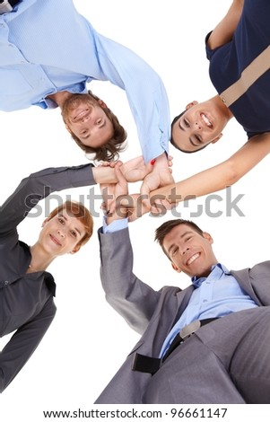 Young businesspeople linking hands, smiling, looking at camera, view from below.?