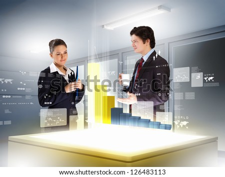 young businesspeople looking at graph of high-tech image