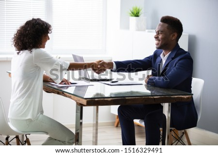 Young Businesspeople Shaking Hands At Interview In Office