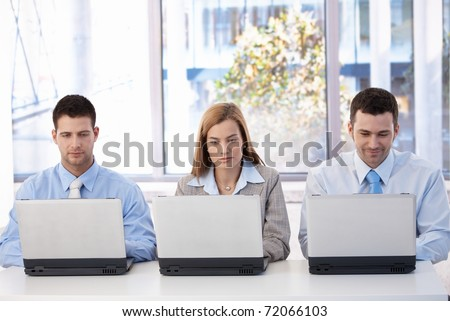 Young businesspeople sitting at desk in bright office, busy by working on laptop.?