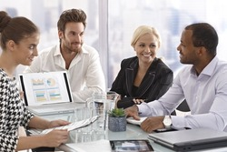 Young businesspeople sitting in meetingroom, having meeting, chatting in good mood.