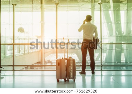 Young businesspeople stand at the airport during sunset and are talking on the phone to inform them of their important business travel overseas. #751629520