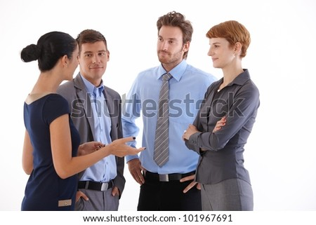 Young businesspeople standing, talking, smiling.
