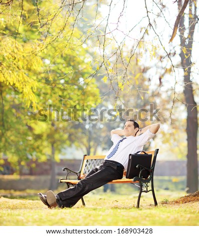 Young businessperson sitting on a wooden bench and relaxing in a park, shot with tilt and shift