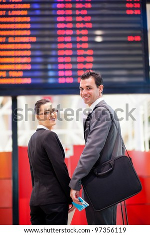 young businesswoman and businessman in front of airport information board