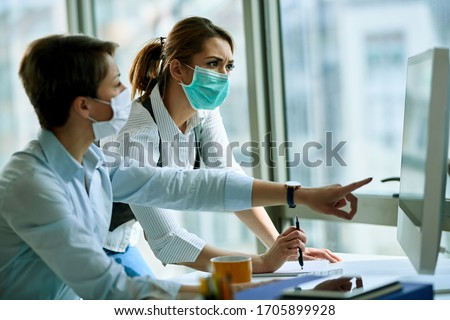 Young businesswoman and her colleague wearing face masks while working on a computer in the office during virus epidemic.