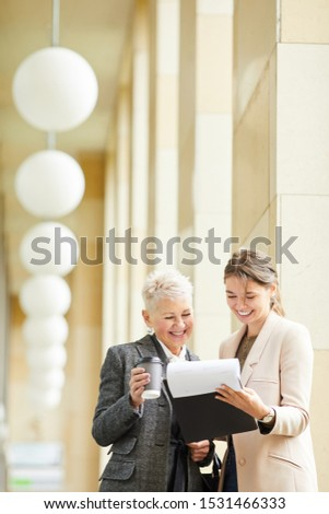 Young businesswoman and mature businesswoman reading a document together and smiling while standing outdoors #1531466333