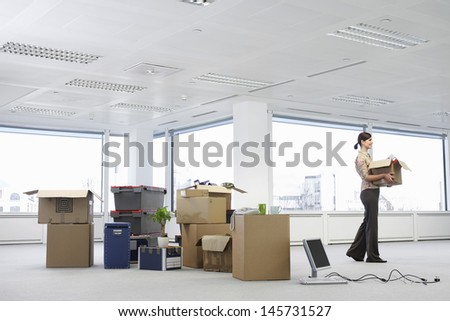 Young businesswoman carrying cardboard box near cartons and equipment in empty office space