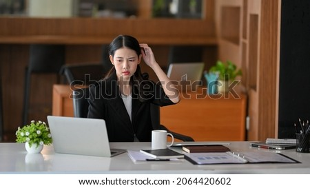 Young businesswoman confused on her work process, have a problems on internet connection on laptop computer.