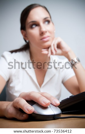 Young businesswoman contemplating. Selective focus on her hand using computer mouse.