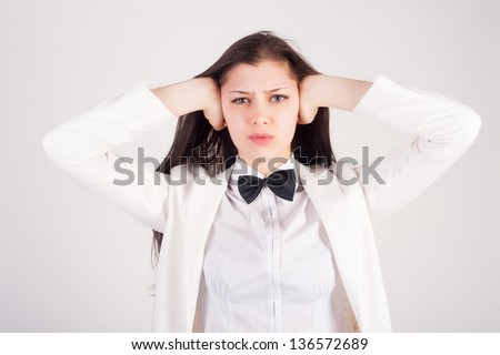 Young businesswoman covering her ears with hands on white background/ No evil hear gesture - stock photo