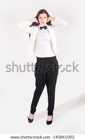 Young businesswoman covering her ears with hands on white background. No evil hear gesture