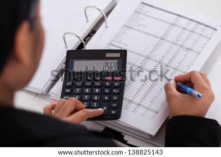 Young Businesswoman Doing Calculations In The Office