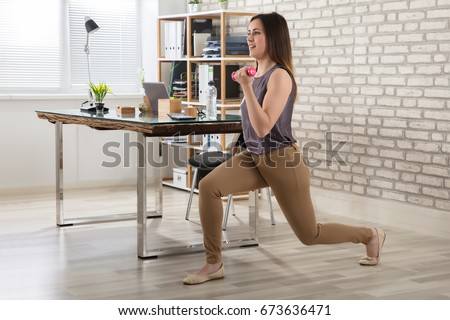 Young Businesswoman Doing Exercise With Fitness Dumbbells In Office #673636471
