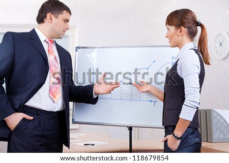 young businesswoman drawing graph on chart to businessman in office