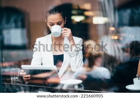 Young businesswoman drinking coffee and using tablet computer in cafe #221660905