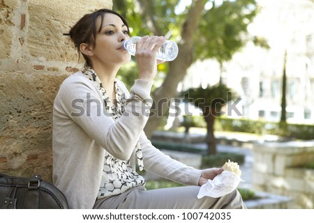 Young businesswoman drinking water from a small plastic bottle while having a lunch break in the park.