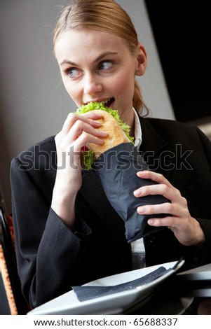 young businesswoman eating a sandwich