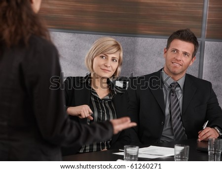 Young businesswoman explaining business problem, others sitting at meeting table, looking at her.?