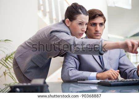 Young businesswoman explaining computer program to colleague