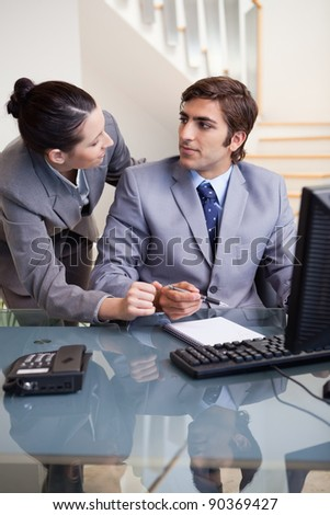 Young businesswoman explaining something to her colleague