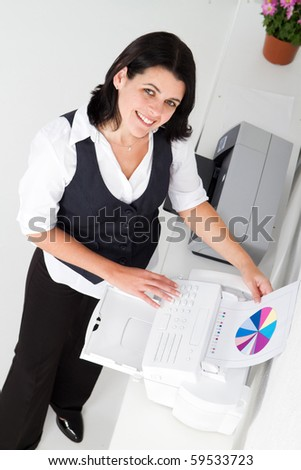 young businesswoman faxing document
