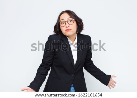 young businesswoman feeling clueless and confused, having no idea, absolutely puzzled with a dumb or foolish look against white wall