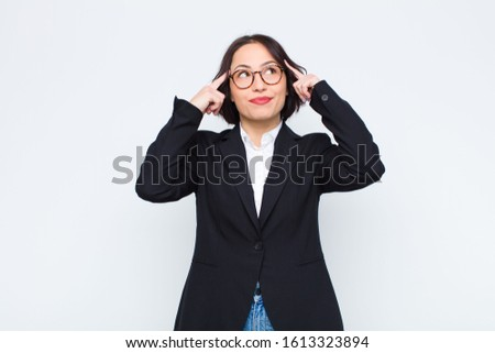 young businesswoman feeling confused or doubting, concentrating on an idea, thinking hard, looking to copy space on side against white wall