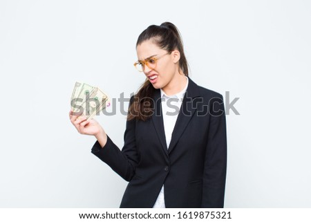 young businesswoman feeling puzzled and confused, with a dumb, stunned expression looking at something unexpected with banknotes with bills