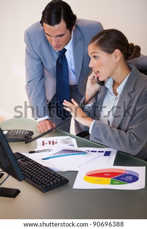 Young businesswoman getting a phone call while analyzing statistics