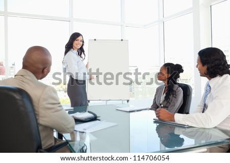 Young businesswoman giving a presentation while her colleagues are listening to her