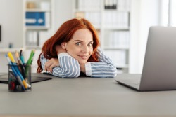 Young businesswoman glancing sideways at the camera as she relaxes resting her arms and head on the desk viewed low angle